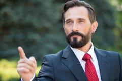 Geschäftsmannpunkt zum Ziel in der Zukunft Mann im Anzug und rote Bindung zeigen Hand vorwärts über grünem Hintergrund im Freien lizenzfreie stockbilder