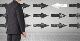 Geschäftsmannrückseite gegen Wand mit Pfeilen Stockbild