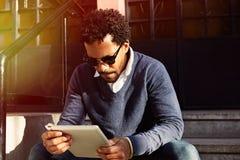 Geschäftsmannreisen, arbeitend in New York Junger schwarzer Mann, der auf Straße, Lesung, Funktion auf elektronischem Gerät stati Lizenzfreies Stockfoto