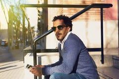 Geschäftsmannreisen, arbeitend in New York Junger schwarzer Mann, der auf Straße, Lesung, Funktion auf elektronischem Gerät stati Lizenzfreie Stockfotografie