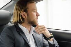 Geschäftsmannreiten im Auto Stockbilder