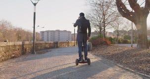 Geschäftsmannreiten segway in der Stadt, die austauschen, um zu arbeiten oder im Haus beim Nennen unter Verwendung des Smartphone stock video