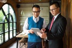 Geschäftsmannschauen und -punktfinger mit zwei Asiaten, um im Notizbuch einzeln aufzuführen, sind sie, sprechend treffend und übe lizenzfreies stockbild