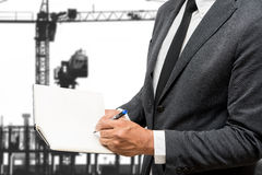 Geschäftsmannschreiben auf Anmerkungsbuch mit Baukran Stockfotografie