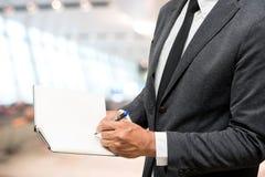 Geschäftsmannschreiben auf Anmerkungsbuch mit Unschärfehintergrund Lizenzfreies Stockbild