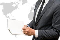 Geschäftsmannschreiben auf Anmerkungsbuch mit wolrd Karte Stockfotografie