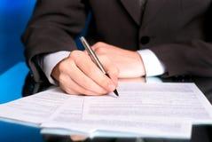 Geschäftsmannschreiben auf einem Formular Lizenzfreie Stockfotos