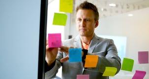 Geschäftsmannschreiben auf klebriger Anmerkung über Glaswand 4k stock video footage