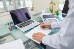 Geschäftsmannschreiben auf Notizbuch während zu Hause arbeiten Stockbild