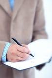 Geschäftsmannschreiben in der Tagesordnung. Stockfoto