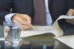 Geschäftsmannschreiben in einem Dokument lizenzfreie stockfotografie