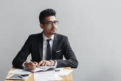 Geschäftsmannschreiben in einem Notizbuch und Blicke weg von der Kamera auf einem grauen Hintergrund Lizenzfreie Stockfotos