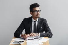 Geschäftsmannschreiben in einem Notizbuch und Blicke weg von der Kamera, der Tablette, Telefon und Papieren auf dem Tisch Stockbilder