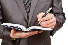 Geschäftsmannschreiben im Geschäftstagebuch Lizenzfreies Stockfoto