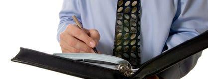 Geschäftsmannschreiben im ledernen Organisator Stockfotografie