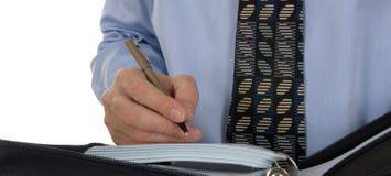 Geschäftsmannschreiben im ledernen Organisator Stockfoto
