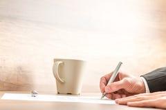 Geschäftsmannschreiben mit einem Stift auf einem Papierblatt Lizenzfreie Stockfotografie