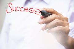 Geschäftsmannschreibens-Erfolgswort mit rotem Stift des weißen Brettes auf whi Stockfotografie