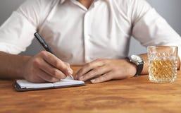 Geschäftsmannschreibensnotizbuch-Schreibenswhisky lizenzfreie stockfotografie