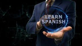 Geschäftsmannshow-Konzepthologramm lernen Spanisch auf seiner Hand stockfotografie