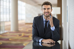 Geschäftsmannsitzen überzeugt mit Lächelnporträt lizenzfreie stockbilder