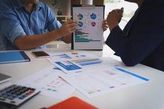 Geschäftsmannsitzung mit neuen Startprojektzeigediagrammdiskussions- und -analysedatendiagrammen und -diagrammen Geschäftsfinanze lizenzfreie stockbilder