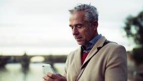 Geschäftsmannstellung auf einer Brücke in der Stadt, unter Verwendung des Smartphone Langsame Bewegung stock video