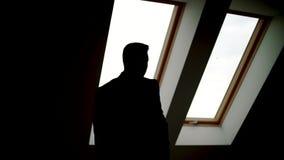 Geschäftsmannstellung nahe bei dem Fenster, heraus schauend Schattenbild des Mannes stock video footage