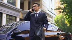 Geschäftsmannstellung nahe dem luxuriösen Auto, das auf dem Smartphone, unglücklich mit Nachrichten spricht stock video footage
