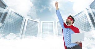 Geschäftsmannsuperheld mit Laptop und der Hand in einer Luft gegen Server und Wolken mit weißer Schnittstelle Stockfotos