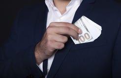 Geschäftsmanntaschengeld in seiner Tasche lizenzfreie stockbilder