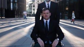 Geschäftsmanntotalisator seins Krüppelkollege im Rollstuhl im Freien stock video footage