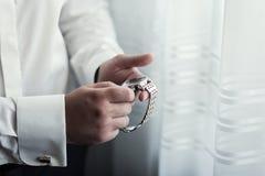 Geschäftsmannuhrkleidung, Geschäftsmann, der Zeit auf seinen wris überprüft Stockbild