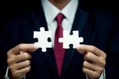 Geschäftsmannversuch, zum zweiteiliges des Puzzlen anzuschließen Lizenzfreie Stockfotos