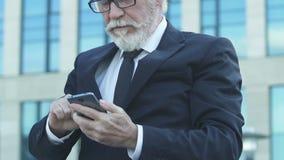 Geschäftsmannvertretung jageste, extrem glücklich über gute Nachrichten vom Smartphone stock video