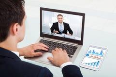 Geschäftsmannvideo-conferencing auf Laptop im Büro Stockfotografie