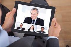 Geschäftsmannvideo-conferencing mit Mitarbeitern auf digitaler Tablette Stockfotografie