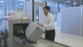 Geschäftsmannwartung Gepäck nach der Überprüfung durch Röntgenstrahlscanner im Flughafen stock video footage