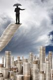 Geschäftsmanstandplatz auf der Geldtreppe Lizenzfreie Stockfotos