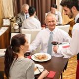 Geschäftsmittagessenkellner, der Rotwein dient Lizenzfreies Stockbild
