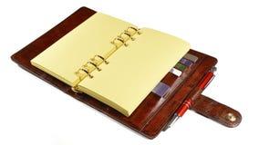 Geschäftsorganisator im braunen Leder mit den leeren Gelben Seiten, die auf dem Tisch legen stockbilder