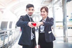 Geschäftspaar übergibt das Halten eines roten Herzens, wir sind in der Liebe, healt Stockfotografie