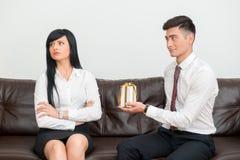 Geschäftspaare, die auf Sofa im Büro sitzen lizenzfreie stockfotos
