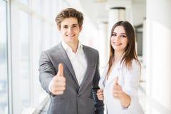 Geschäftspaare, die Daumen oben im Geschäftslokal zeigen Geschäftsfrau und Geschäftsmann greift oben ab Lizenzfreies Stockfoto