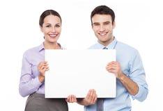Geschäftspaare, die ein Plakat halten lizenzfreie stockfotografie