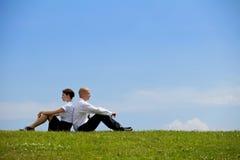 Geschäftspaare, die zurück zu Rückseite auf Gras sitzen Lizenzfreies Stockfoto