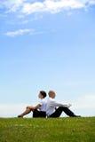 Geschäftspaare, die zurück zu Rückseite auf Gras sitzen Lizenzfreie Stockbilder