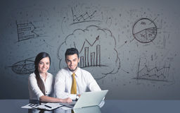 Geschäftspaare mit Geschäftsdiagrammen Stockbild