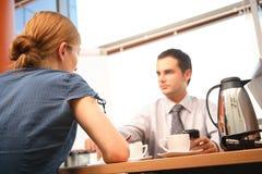 Geschäftspaarschwätzchen in einem Büro lizenzfreie stockbilder