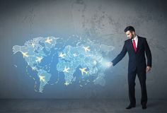 Geschäftsperson, die auf der ganzen Welt digital erzeugte Karte mit Flächen zeigt Stockfotografie